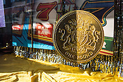 A large model of a British one pound coin in the window display of a Cashino amusement arcade in Lewisham, London, United Kingdom.