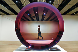 "© Licensed to London News Pictures. 25/09/2018. LONDON, UK. A gallery staff member walks by ""Untitled (Parabolic Lens)"", 1971, by Fred Eversley. Preview of ""Space Shifters"" at the Hayward Gallery, an exhibition which features artworks by 20 leading international artists that disrupt the visitor's sense of space and alter their perception of their surroundings.  The show runs 26 September to 6 January 2019.  Photo credit: Stephen Chung/LNP"