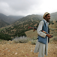 20th August 2007.Tora Bora.A local man armed with a Kalashnikov acts as a body guard for a Tribal leader making a visit to Tora Bora on the 20th August 2007. Tora Bora was one of the mountain hideouts of Osama Bin Laden and the Al-Qaeda fighters. It was destroyed during the battle of Tora Bora at the beginning of this recent conflict.  In the past weeks it has been the scene of a joint US and Afghan offensive against Taliban fighters who have moved back into the area....