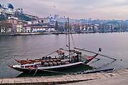 Oporto, December 2012. A boat docked at Douro river loaded with barrels. Vila Nova de Gaia on background.