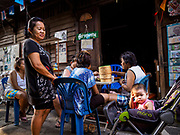 21 MARCH 2017 - BANGKOK, THAILAND: A toddler sits on the edge of a group of women who gather for morning gossip and coffee in Pom Mahakan. They are among the last people living in the old fort. The final evictions of the remaining families in Pom Mahakan, a slum community in a 19th century fort in Bangkok, have started. City officials are moving the residents out of the fort. NGOs and historic preservation organizations protested the city's action but city officials did not relent and started evicting the remaining families in early March.               PHOTO BY JACK KURTZ