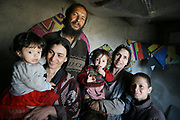 Noor Agha, about 52, stands with his two wives, Farida, 33, the second wife, second from left, and Marzia, 46, the first wife, second from right, with three of their 11 children in his house, Kabul, Afghanistan, Tuesday, March, 13, 2007. Noor Agha is a renowned kite maker who made kites for the movie makers of the best-selling novel, The Kite Runner, which will be distributed by Dreamworks and Paramount Vantage in Nov. this year. Noor Agha's wives, using their special glue, help him produce enough kites to please the clients' needs. Some of his children can also make their own kites with plastic bags and bamboo sticks. As the Afghan New Year's Day (Nawruz) approaching on March 21, the finger tips of Noor Agha's family got busier for mass production.