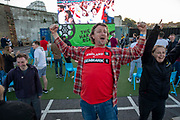 An England fan wearing a 2-1 score prediction on his t-shirt celebrating a goal during the Euro 2020 semi final match between England and Denmark on the 7th of July 2021 at the outdoor screen at Folkestone Harbour Arm, in Folkestone, United Kingdom.