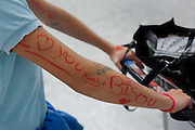 """A close-up detail of teenage words, written in marker pen on a young person's arm in the departures concourse of Heathrow Airport's Terminal 5. Holding the handles of her baggage trolley that has an open bag in which we see some possessions, the girl displays the words 'I (heart) love you' and the name of Kentin Bisou. It may be a declaration of true love or just a teenage prank before an adventure starts from this aviation hub. From writer Alain de Botton's book project """"A Week at the Airport: A Heathrow Diary"""" (2009). ."""