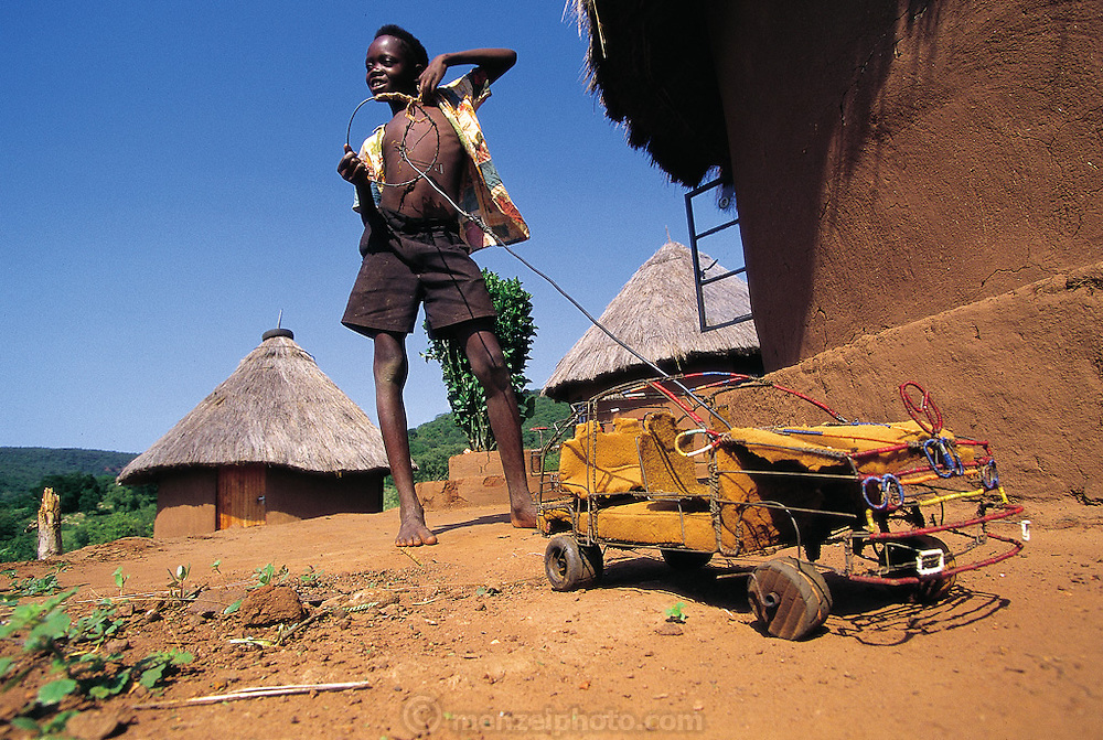 Thirteen-year-old Venda youth, Azwifarwi, with his homemade Mercedes crafted ingeniously and artistically out of scrap wire, foam rubber and wood in order to push and steer around his village, Mpumalanga, South Africa. (Man Eating Bugs page 140,141)