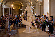 """Tourists admire the statue of Diana of Versailles, a slightly over lifesize marble statue of the Greek goddess Artemis (Latin: Diana), with a deer, located in the Musée du Louvre, Paris. It is a Roman copy (1st or 2nd century AD) of a lost Greek bronze original attributed to Leochares, c. 325 BC. The statue is also known as Diana à la Biche, Diane Chasseresse (""""Diana Huntress""""), Artemis of the Chase, and Artemis with the Hind."""