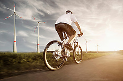 Mature man riding electric bicycle with wind turbine at sunset, Bavaria, Germany