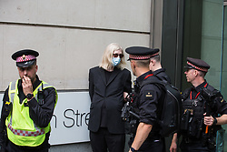 London, UK. 27th August, 2021. City of London Police arrest an environmental activist from Extinction Rebellion who spread fake blood outside the offices of law firm Debevoise & Plimpton LLP during a Blood Money March through the City of London on the fifth day of Impossible Rebellion protests. Extinction Rebellion were intending to highlight financial institutions funding fossil fuel projects, especially in the Global South, as well as law firms and institutions which facilitate them, whilst calling on the UK government to cease all new fossil fuel investment with immediate effect.