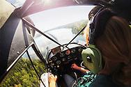 A female pilot flies her float plane down for landing on a remote Alaskan lake.