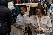 Sheltering under a shopping bag, two women hurry through Londons streets during unseasonal June showers, on 15th June 2019, in London, England.