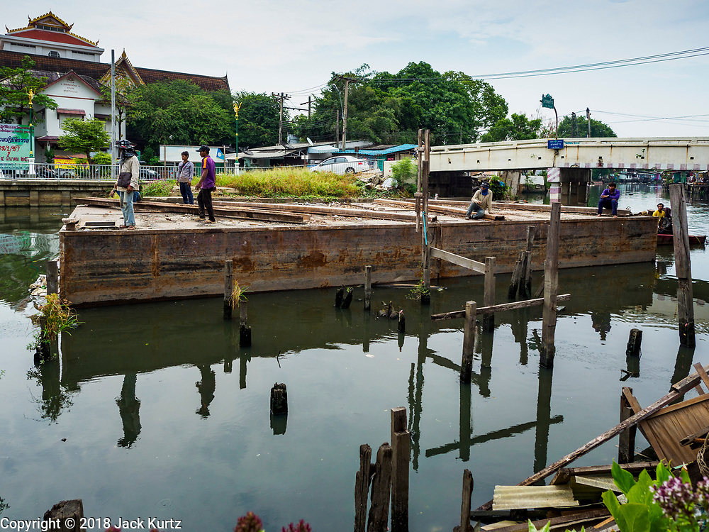 """22 MARCH 2018 - BANGKOK, THAILAND: A barge goes up Khlong Lat Phrao past a demolished home site. Bangkok officials are evicting about 1,000 families who have set up homes along Khlong  Lat Phrao in Bangkok, the city says they are """"encroaching"""" on the khlong. Although some of the families have been living along the khlong (Thai for """"canal"""") for generations, they don't have title to the property, and the city considers them squatters. The city says the residents are being evicted so the city can build new embankments to control flooding. Most of the residents have agreed to leave, but negotiations over compensation are continuing for residents who can't afford to move.      PHOTO BY JACK KURTZ"""