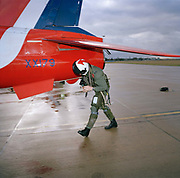 Flight Lieutenant Simon Stevens, a pilot in the elite 'Red Arrows', Britain's prestigious Royal Air Force aerobatic team, makes a pre-flight check of his Hawk jet aircraft before a practice flight at RAF Scampton. Stevens and his fellow-aviators fly up to 6 times in winter training, learning new manoeuvres. The dangers of high-speed close formation flight makes health and safety precautions vital; the Ministry of Defence (MoD) and the Royal Air Force take working environments of their personnel seriously so pre-flight examination of aircraft happens before every sortie (flight). Performing the brief safety walk-around, Stevens bends at the waste to avoid the aeroplane's low aileron despite wearing a helmet, full flying suit, boots, life-vest and anti-g-pants. Flying still continues despite rain clouds in the gloomy Lincolnshire sky.