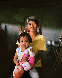 """Teresita """"Tita"""" Comodaz poses with her granddaughter Precious Lara in Cavite, Philippines on Dec. 2006.  Teresita and Demetrio """"Emmet"""" Comodaz take care of their granddaughter while their daughter Rosalie Villanueva, 35, works as a nurse in the United Arab Emirates. Emmet spent most of his life working in Saudi Arabia and his earnings, and those of his daughter, have enabled the family to move out of the slums in Manila and into a large home in a neighboring town.  Each year, the Philippines exports more than a million of its nationals to work abroad through its overseas employment program. Others leave to become permanent residents of their country of destination. Overseas Filipino Workers (OFWs) typically work as doctors, accountants, IT professionals, entertainers, teachers, nurses, engineers, military servicemen, students, domestic helpers and caregivers throughout the world, but primarily work in the Middle East and Gulf countries."""
