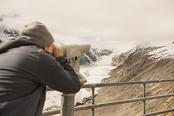 Mature man looking at view with telescope, Pasterze glacier, National Park Hohe Tauern, Carinthia, Austria