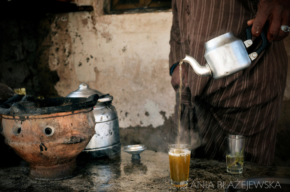 Morocco. Man pouring the a la menthe from a teapot.