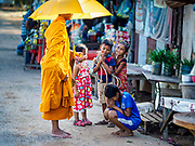 "15 FEBRUARY 2019 - SIHANOUKVILLE, CAMBODIA:  Children prevent alms to a Buddhist monk in a migrant camp in Sihanoukville. Families who live in the shanty town came to Sihanoukville from other Cambodian provinces because of the town's booming economy and construction industry building Chinese resorts and casinos. There are about 80 Chinese casinos and resort hotels open in Sihanoukville and dozens more under construction. The casinos are changing the city, once a sleepy port on Southeast Asia's ""backpacker trail"" into a booming city. The change is coming with a cost though. Many Cambodian residents of Sihanoukville  have lost their homes to make way for the casinos and the jobs are going to Chinese workers, brought in to build casinos and work in the casinos.     PHOTO BY JACK KURTZ"