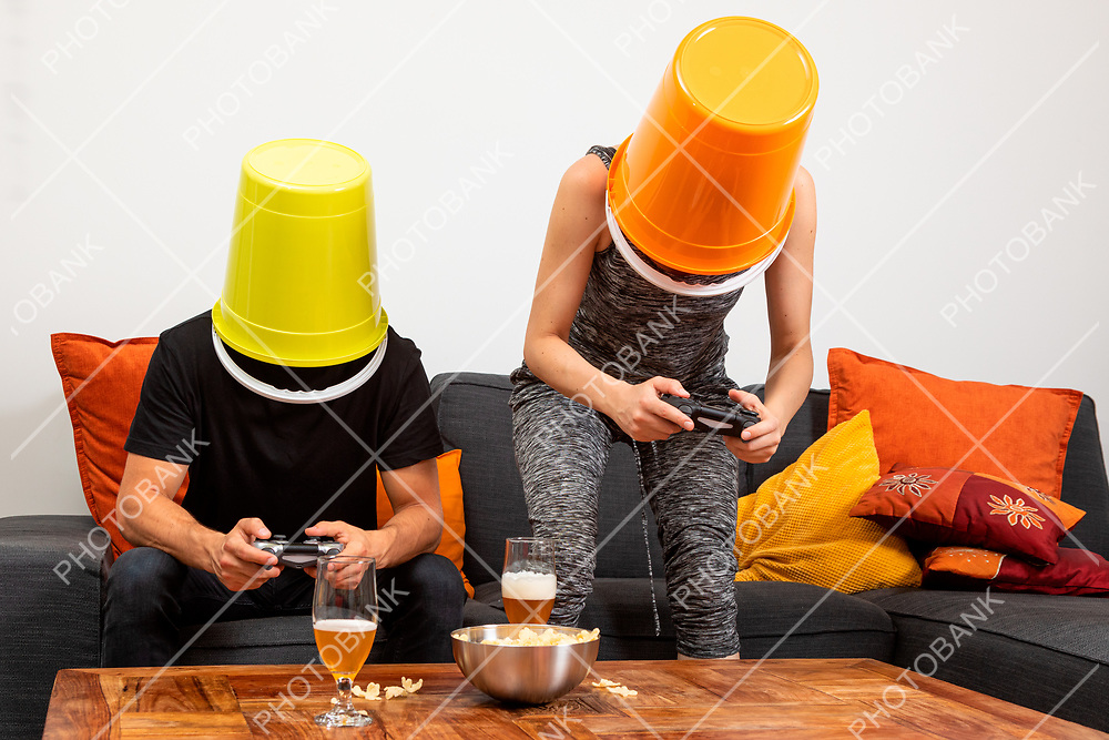 Young couple play video games sitting comfortably on the sofa at home. They drink beer and eat chips