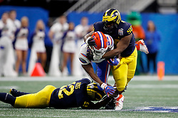 Florida Gators running back Lamical Perine #22 is tackled by Michigan Wolverines defensive lineman Michael Dwumfour #50 during the Chick-fil-A Peach Bowl, Saturday, December 29, 2018, in Atlanta. ( Paul Abell via Abell Images for Chick-fil-A Peach Bowl)