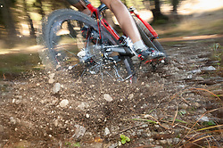 Mountainbiker brakes hard and stones are splashing, Bavaria, Germany
