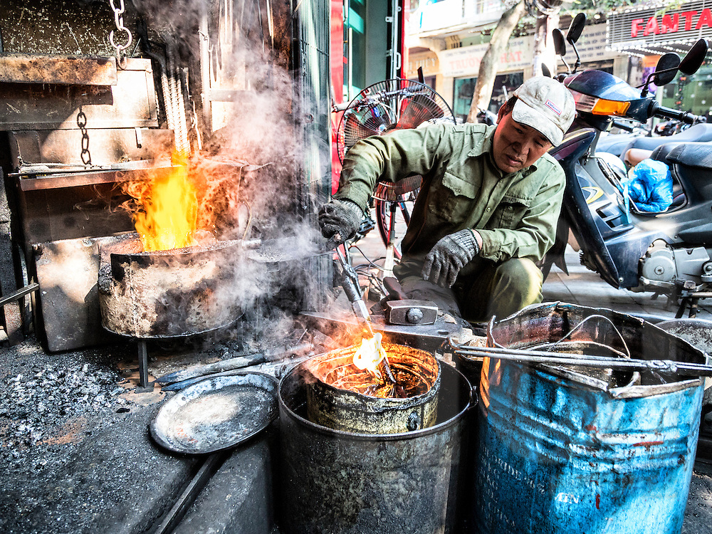A blacksmith forges metal products along Lo Ren street in Hanoi's Old Quarter, Vietnam