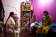 A female outreach worker from Operation Asha visits Indian households in Delhi, India.  She is doing active case finding, trying to discover people who are suffering from pulmonary Tuberculosis (TB) who are highly infectious to others especially those who live in overcrowded and poorly ventilated housing. Here she talks to a father about his cough while his wife and small child listen.