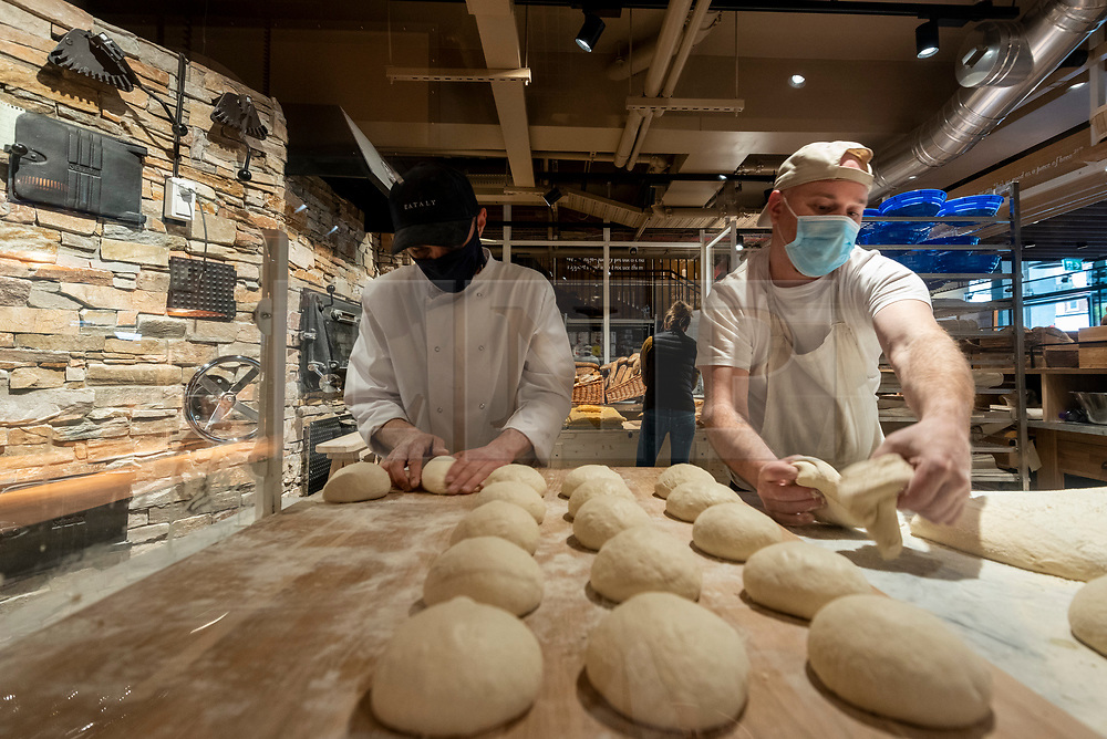© Licensed to London News Pictures. 30/04/2021. LONDON, UK. Bakers prepare fresh bread as Eataly London opens in Bishopsgate.  The huge store is the first one to open in the UK and joins 42 others around the world in celebrating the cuisine of Italy with food counters, production labs, restaurants (open when lockdown restrictions allow) and an open market place for customers to participate in an innovative food and beverage experience.  Photo credit: Stephen Chung/LNP