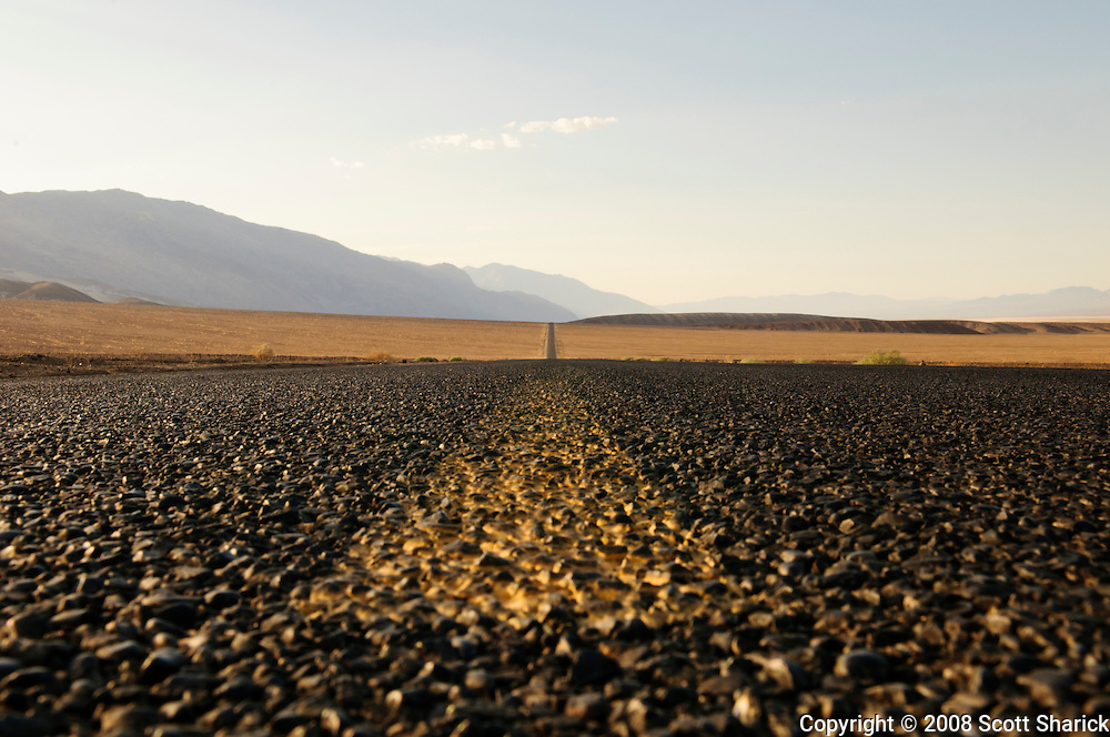 A long lonely road in the middle of Death Valley showing a closeup of the yellow center lane and the stone in the pavement.