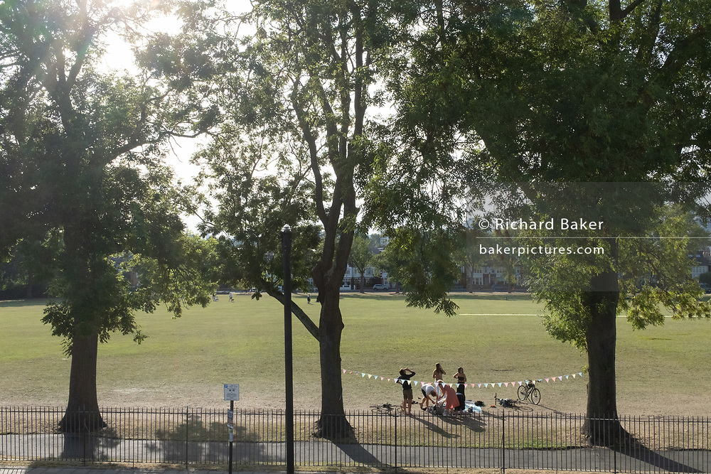 A birthday party takes place between ash trees during the Coronavirus pandemic in Ruskin Park in the south London borough of Lambeth, on 29th July 2020, in London, England.