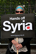 Demonstration against any intervention in Syria called by Stop the War and CND, August 30th 2013, Central London. A Muslim woman wearing a headscarf and sunglasses holds a placard saying 'Hands off Syria'.