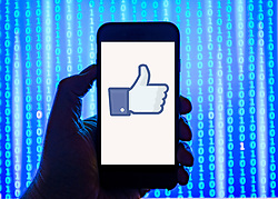 Person holding smart phone with Facebook Like   logo displayed on the screen. EDITORIAL USE ONLY