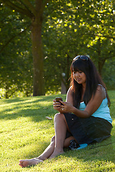 North America, United States, Washington, Bellevue, Bellevue Downtown Park, woman using phone in park.  MR