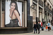 Large scale Burberry luxury brand advertising images in shop windows along Regent Street on 26th May 2021 in London, United Kingdom. Passing people interact with the huge figures in these photographs as if tiny in comparison. This area of the capital is known for its exclusive shops whose vrands are aimed at the rich and wealthy.