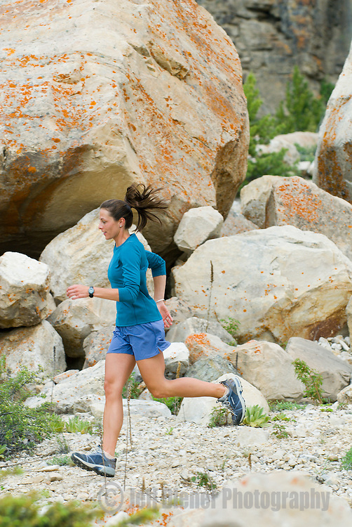 A young woman trail running in the Gros Ventre Mountains of Jackson Hole, Wyoming.