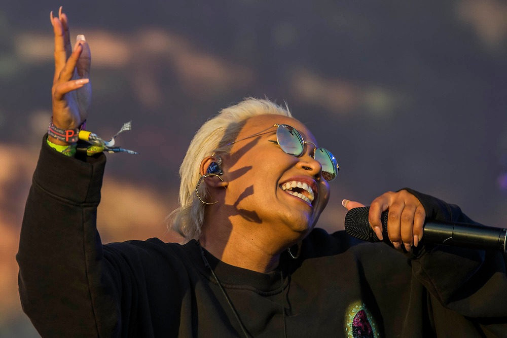 The sun sets on the 2017 Glastonbury Festival as Emeli Sande plays the other Stage - her reflective glasses show the red sky and the crowd. Worthy Farm. Glastonbury, 25 June 2017