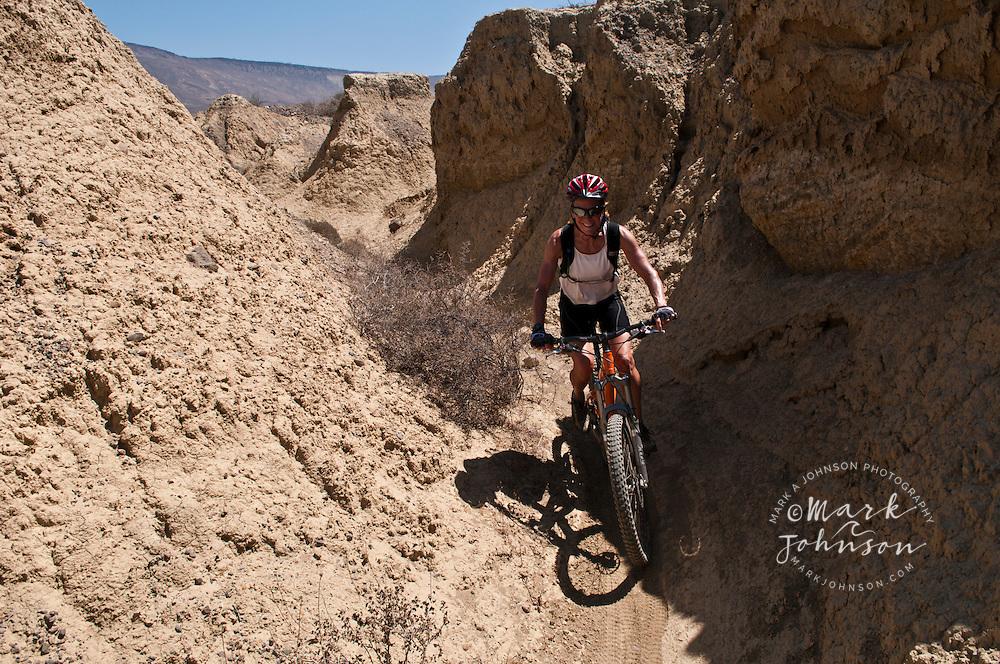 Woman mountain biking in the Badlands, Punto San Carlos, Baja California, Mexico ****Model Release available