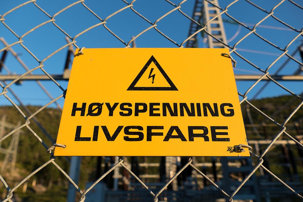 Gult skilt ved transformatoranlegg som advarer om høyspenning og livsfare.