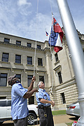 Willie Townesend,left and Joe Brown both employees of the Mississippi State Capitol are seen raising and lowering commemorative State flags. They raised and lowered over 100 flags today, that have been purchased by people from all around the world, and they have each flown over the Capitol, just hours before Governor Tate Reeves signed a historic Bill HB1796 decommissioning the state flag and opening the door to a new flag without the Confederate emblem that has flown for 126 years.<br /> <br /> A Mississippi flag flies at the governors mansion in Jackson, Mississippi, U.S., June 30, 2020.  Photo©Suzi Altman