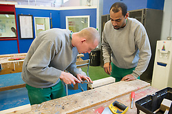 A prisoner learning the carpentry trade in a workshop
