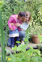 Single mother and young daughter looking into garden pond,