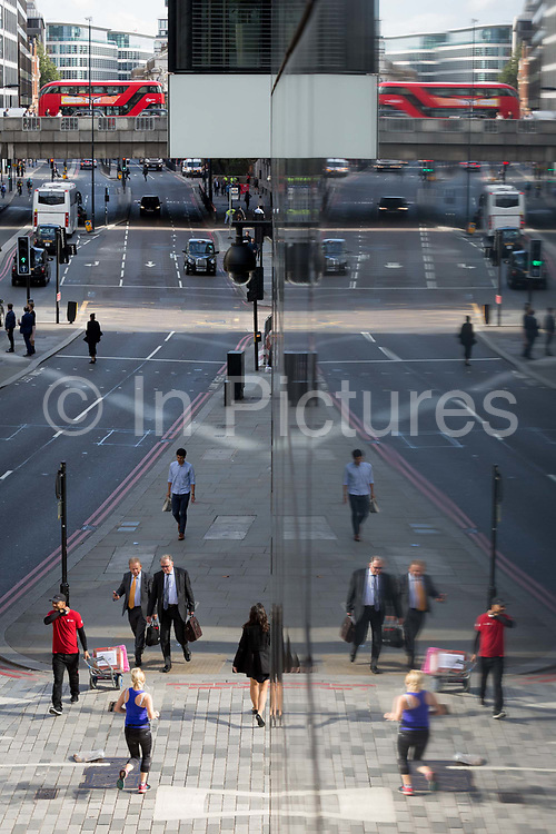 An aerial cityscape of Londoners and traffic on Upper Thames Street upstream from London Bridge in the City of London - the capitals financial district, on 11th October 2018, in London, England.