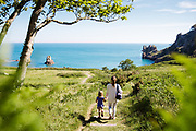 Mum and child walking down the grassy path that leads to the hidden cove, Beauport beach, a beautiful bay on the south coast of Jersey, great for swimming, paddle boarding and kayaking.