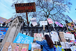 "© Licensed to London News Pictures. 23/03/2019. LONDON, UK.  Signs affixed to the railings of the Houses of Parliament after people took part in the ""Put It To The People March"", on what was supposed to be six days before the UK was due to leave the EU, before an extension to the departure date was given.  Protesters demand that the public is given a final say on Brexit as support for the Prime Minister's withdrawal plan continues to recede.  Photo credit: Stephen Chung/LNP"