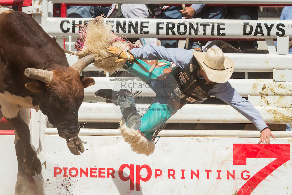 Bull rider Lon Danley of Tularosa, New Mexico is thrown from I'm Your Huckleberry at the Cheyenne Frontier Days rodeo at Frontier Park Arena July 24, 2015 in Cheyenne, Wyoming. Frontier Days celebrates the cowboy traditions of the west with a rodeo, parade and fair.
