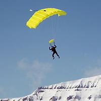 A polar parasailer floats through arctic cold above Spitsbergen Island.