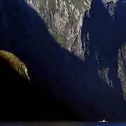A tourist cruise ship dwarfed by the steep cliff faces of Milford Sound, South Island, New Zealand. .Milford Sound (Piopiotahi in Ma¯ori) is a fjord in the south west of New Zealand's South Island, within Fiordland National Park and the Te Wahipounamu World Heritage site. It has been judged the world's top travel destination and is acclaimed as New Zealand's most famous tourist destination..Milford Sound runs 15 kilometres inland from the Tasman Sea at Dale Point - the mouth of the fiord - and is surrounded by sheer rock faces that rise 1,200 metres (3,900 ft) or more on either side. Among the peaks are The Elephant at 1,517 metres (4,977 ft), said to resemble an elephant's head and The Lion, 1,302 metres (4,272 ft), in the shape of a crouching lion. Lush rain forests cling precariously to these cliffs, while seals, penguins, and dolphins frequent the waters and whales can be seen sometimes..Milford Sound sports two permanent waterfalls all year round, Lady Bowen Falls and Stirling Falls. After heavy rain many hundreds of temporary waterfalls can be seen running down the steep sided rock faces. .The beauty of this landscape draws thousands of visitors each day, with between 550,000 and 1 million visitors in total per year. This makes the sound one of New Zealand's most-visited tourist spots, and also the most famous New Zealand tourist destination.  Milford Sound, New Zealand. 29th April 2011. Photo Tim Clayton
