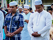 """22 AUGUST 2018 - GEORGE TOWN, PENANG, MALAYSIA: Men pray during Eid al-Adha services at Kapitan Keling Mosque in George Town. It is the oldest mosque in George Town. Eid al-Adha, """"Feast of the Sacrifice"""" is the second of two Islamic holidays celebrated worldwide each year. It honors the willingness of Ibrahim (Abraham) to sacrifice his son as an act of obedience to God's command.     PHOTO BY JACK KURTZ"""