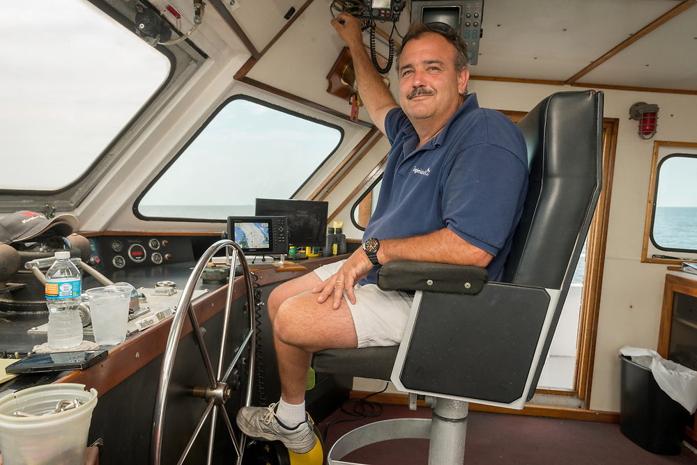August 4, 2017 - Tangier Island, VA - Captain Stephen Thomas aboard the ship of the same name that he uses to ferry passengers to the Cheseapeake Bay's Tangier Island 7 days a week from May to October.  He steers the ship with his foot while narrating about the sigths to the passengers.  After 9/11 Captain Thomas he piloted the boat up to New York to assist commuters on their daily commutes when subway service in lower Manhattan was shut down.  The boat has been in service since 1982. Photo by Susana Raab/Institute