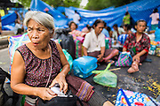 "11 MAY 2013 - BANGKOK, THAILAND:   Women from the Thai countryside sit in the road in front of Government House. Several hundred small scale family farmers camped out ""Government House"" (the office of the Prime Minister) in Bangkok to Thai Prime Minister Yingluck Shinawatra to deliver on her promises to improve the situation of family farmers. The People's Movement for a Just Society (P-move) is a network organization which aims strengthen the voices of different, but related causes working to bring justice for marginalized groups in Thailand, including land rights for small-scale farmers, citizenship for stateless persons, fair compensation for communities forced to relocate to accommodate large scale state projects, and housing solutions for urban slum dwellers, among others.   PHOTO BY JACK KURTZ"