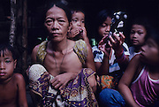 PENAN FAMILY, MALAYSIA. Sarawak, Borneo, South East Asia. Penan family, child with toy  car. Tropical rainforest and one of the world's richest, oldest eco-systems, flora and fauna, under threat from development, logging and deforestation. Home to indigenous Dayak native tribal peoples, farming by slash and burn cultivation, fishing and hunting wild boar. Home to the Penan, traditional nomadic hunter-gatherers, of whom only one thousand survive, eating roots, and hunting wild animals with blowpipes. Animists, Christians, they still practice traditional medicine from herbs and plants. Native people have mounted protests and blockades against logging concessions, many have been arrested and imprisoned.