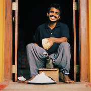 A man sits and grinds two halves of a coconut in Sri Lanka